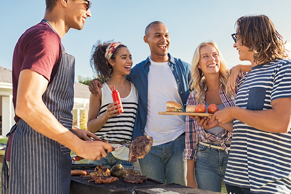 friends hanging out by a grill with food